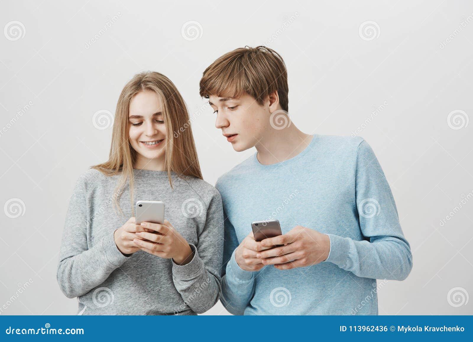 Två positiva vänner som redigerar selfie för att posta den i socialt nätverk Vänliga älska par, flickvänvisningpojkvän