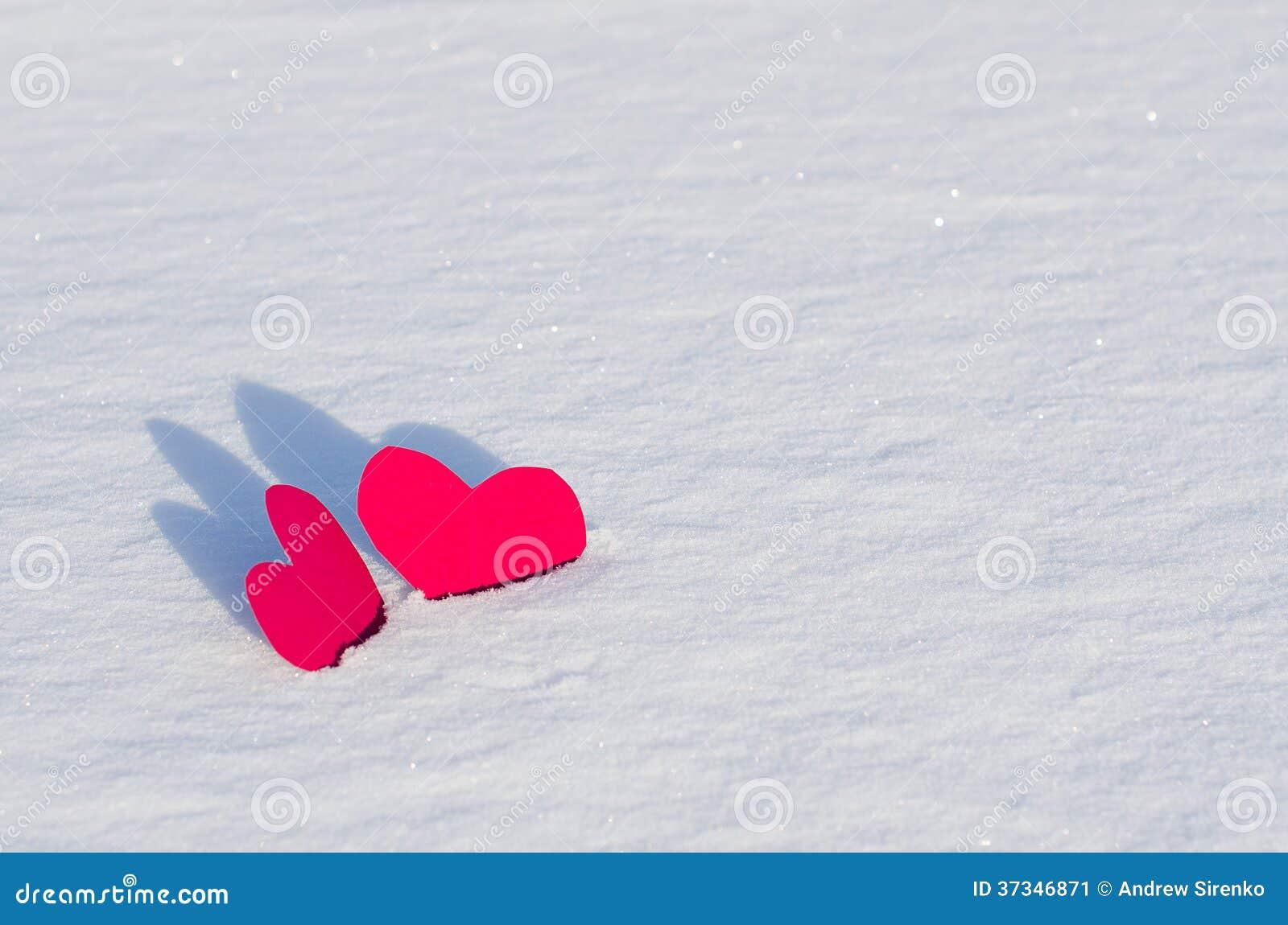 Två röda hjärtor i snö