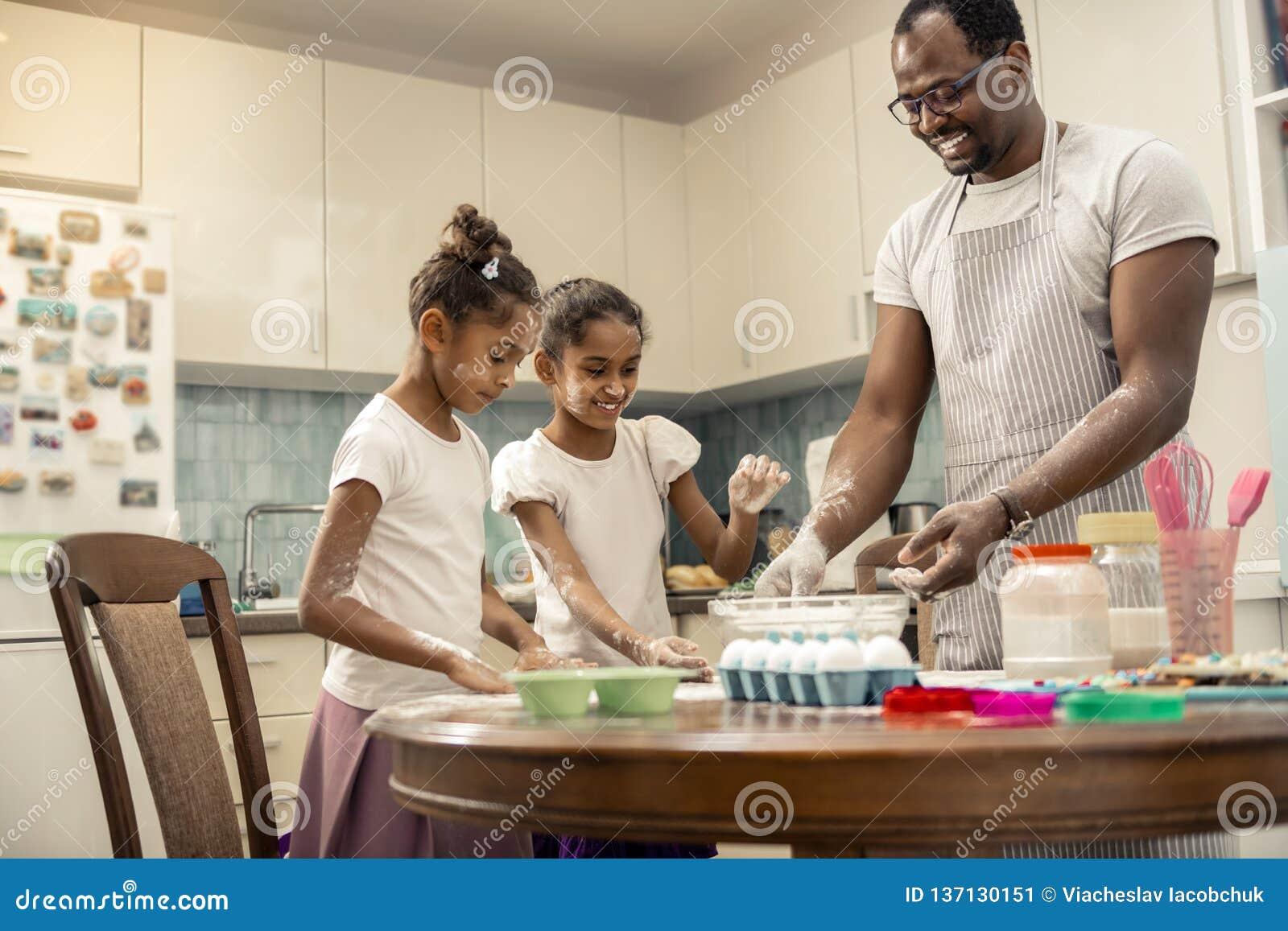 Två roliga flickor som lagar mat pajen med deras älska hjälpsamma fader