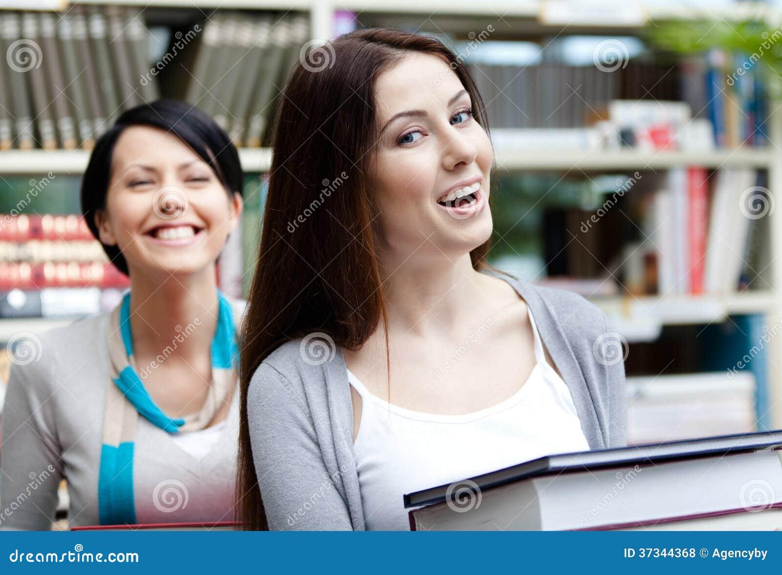 Två skratta flickvänner bär böcker