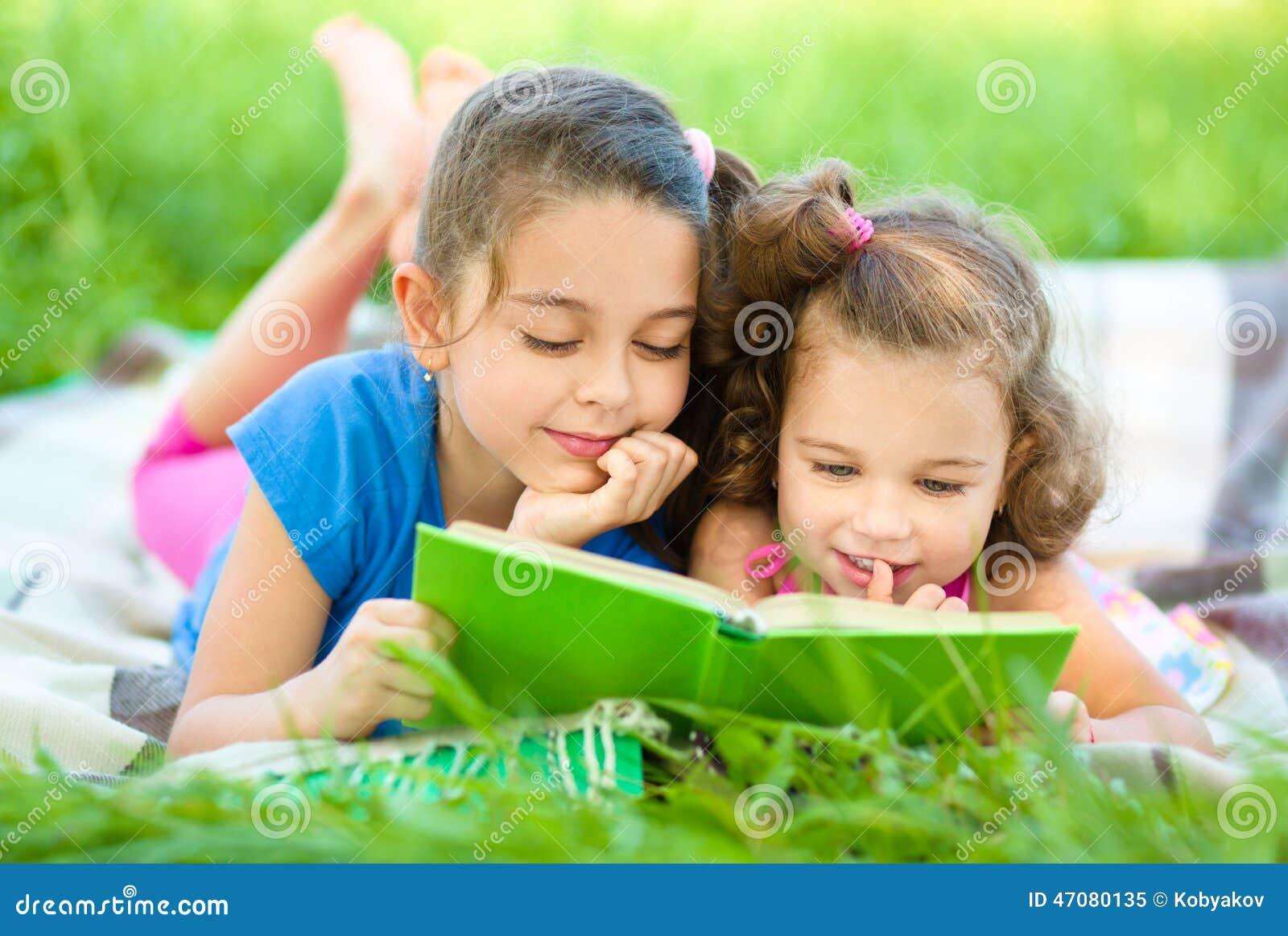 Två små flickor är läseboken