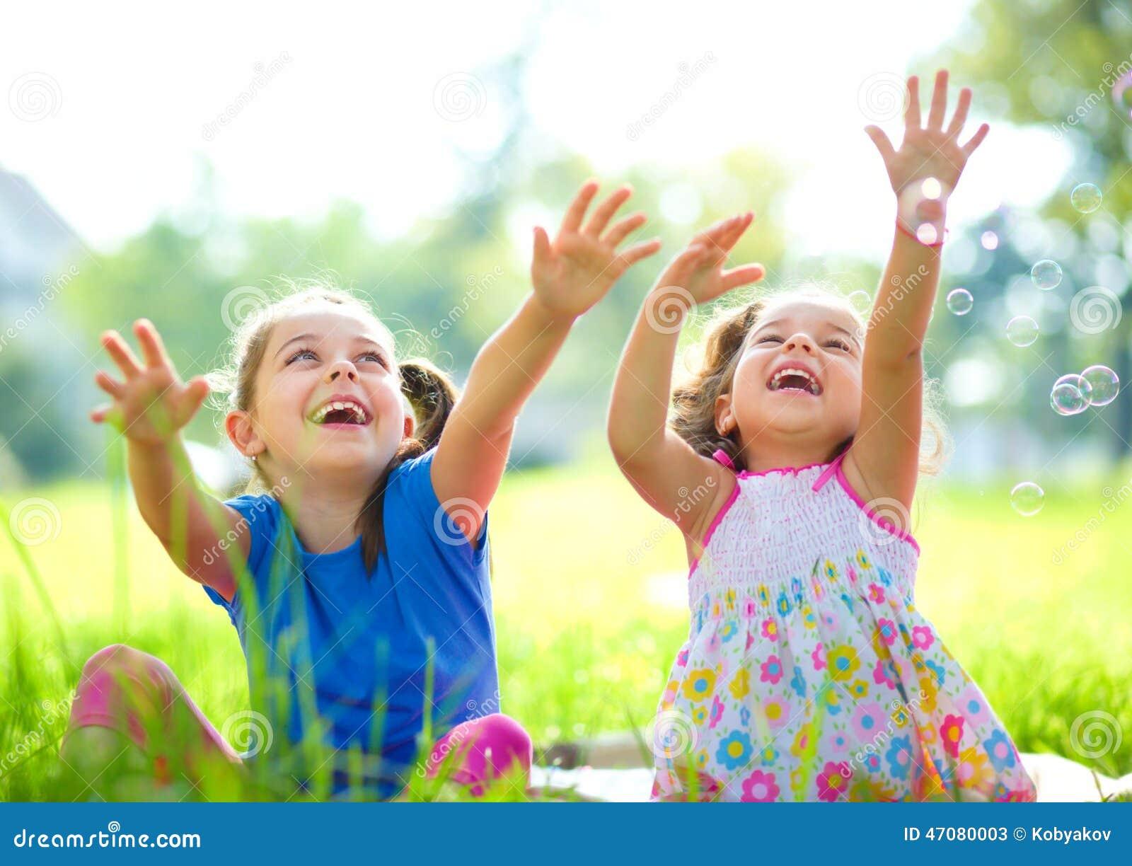 Två små flickor fångar såpbubblor