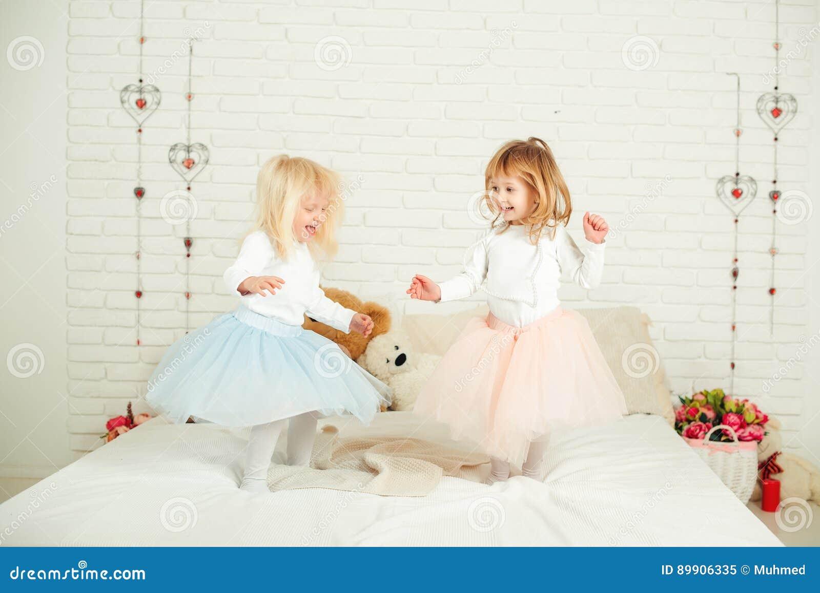 Två små flickor i trevliga klänningar i rolig banhoppning på en säng