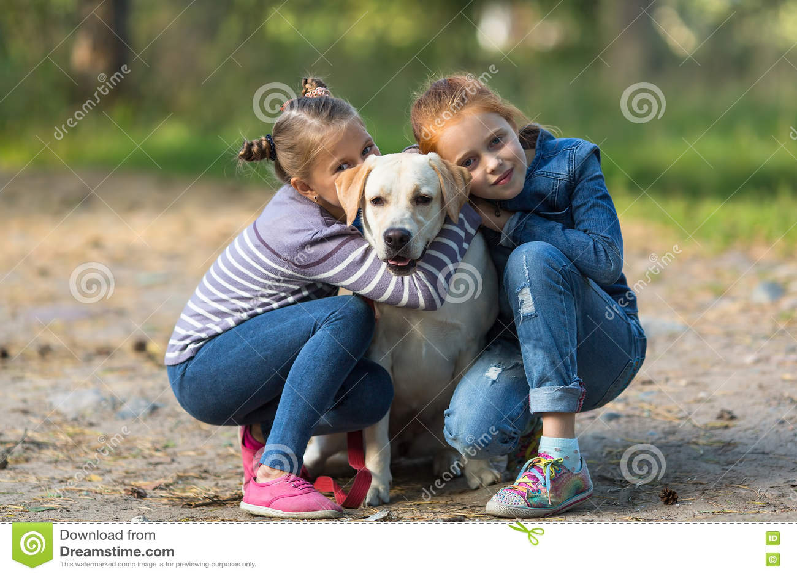 Två små flickor med hunden utomhus lekar