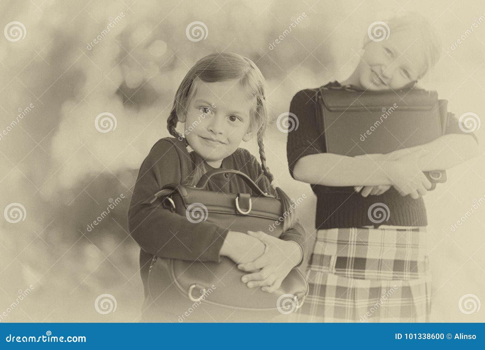 Två små flickor ordnar till tillbaka till skolacloseupen, höstdag