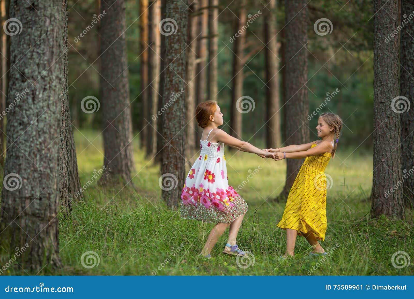 Två små flickor som har gyckel som spelar tillsammans i en parkera