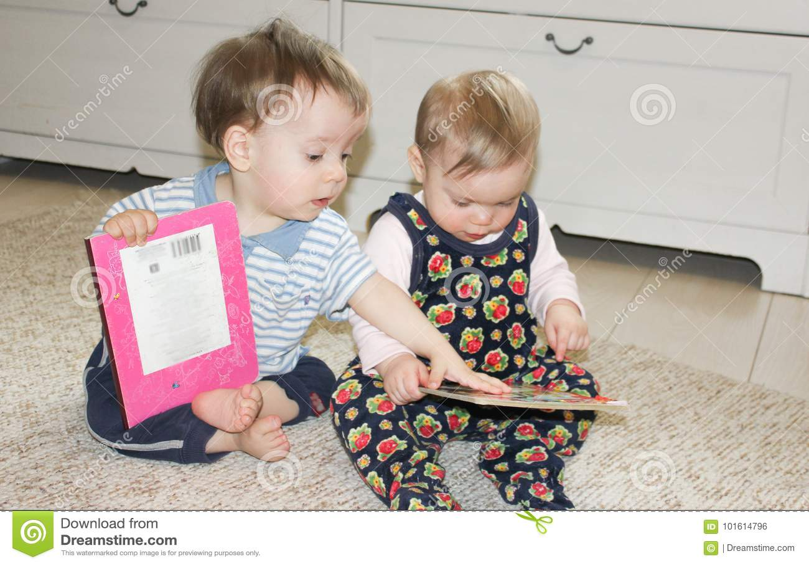 Två småbarn sitter på golvet och läser böcker Flicka och pojke