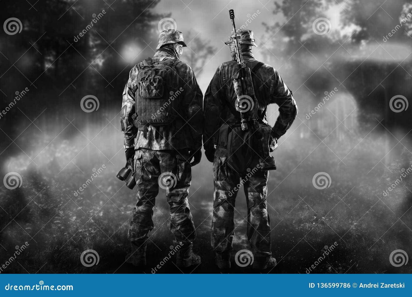 Två soldater av en special enhet står i en rökig skog
