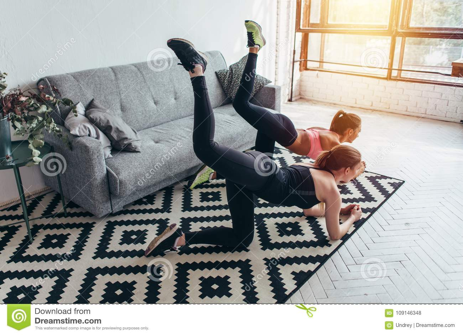 Två sportive kvinnliga vänner som gör den utförande åsnan för ändetoningövningen, sparkar hemma