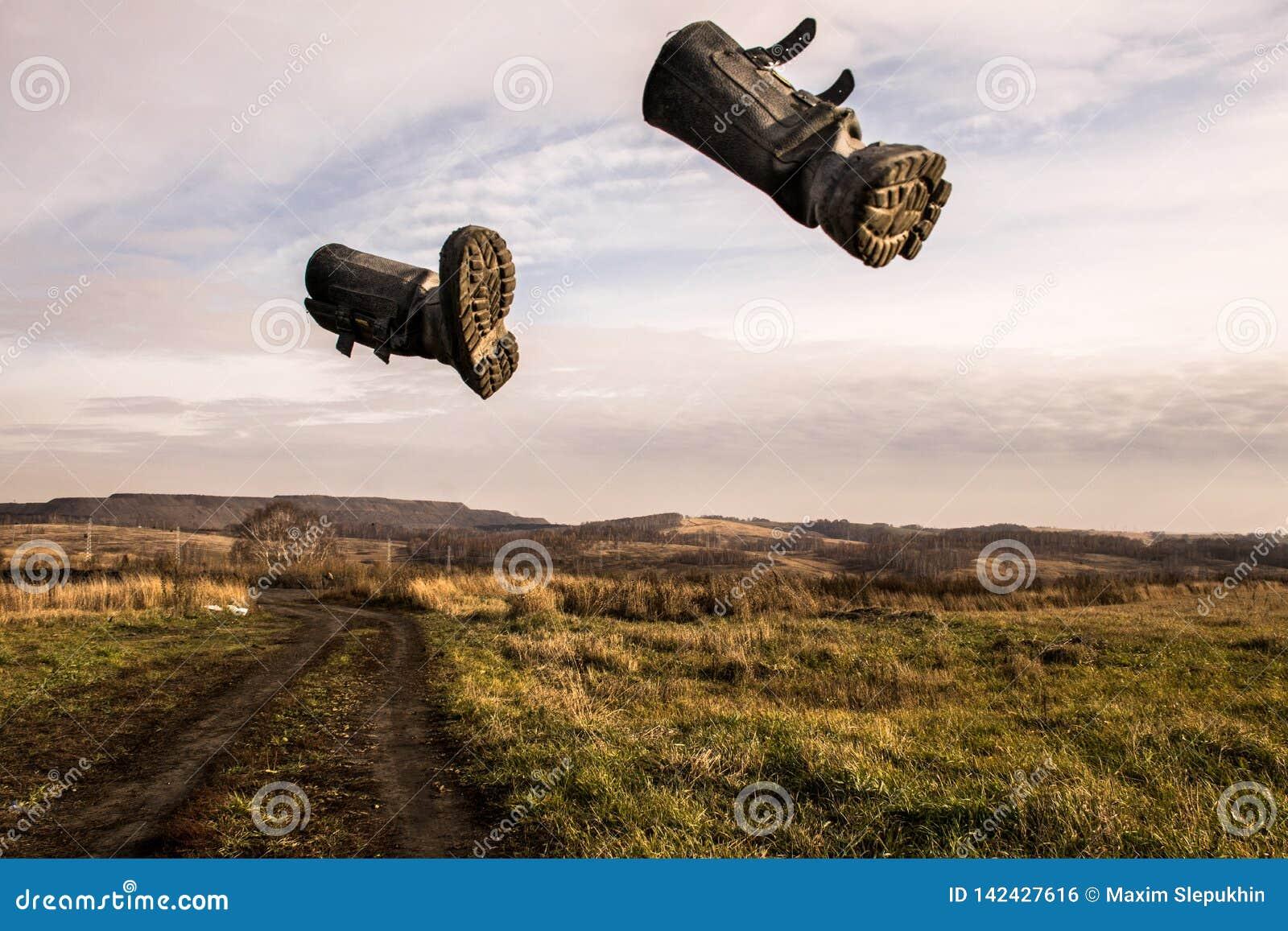 Två svarta kängor flyger över himlen i mitt av ett höstfält