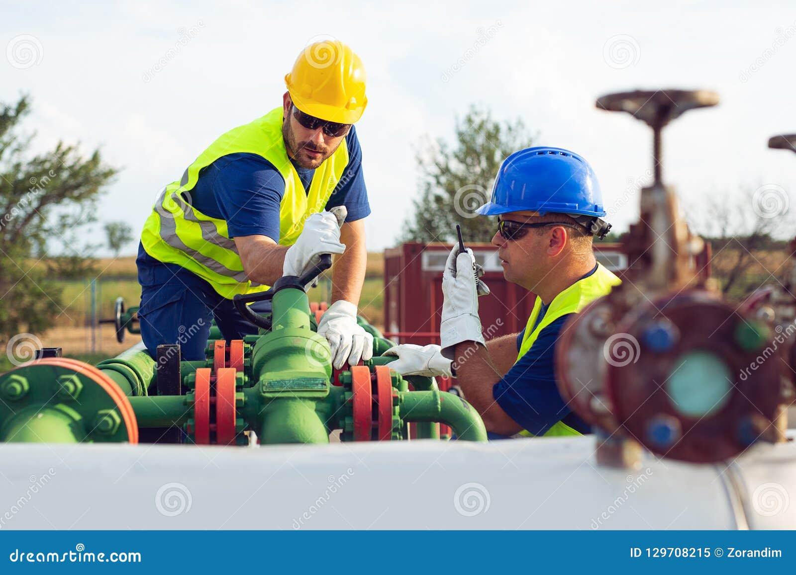 Två teknikerer som arbetar inom fossila bränslenraffinaderi