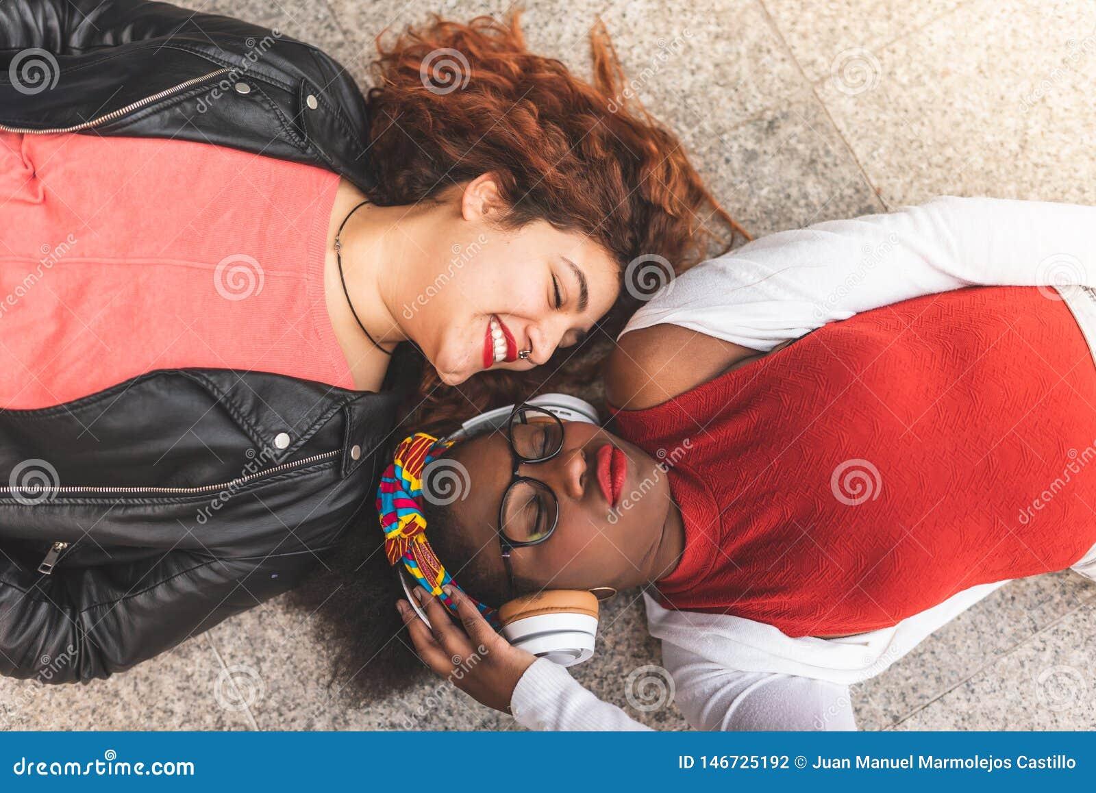 Två tonårs- flickor som ner lägger och ser sig på golvet