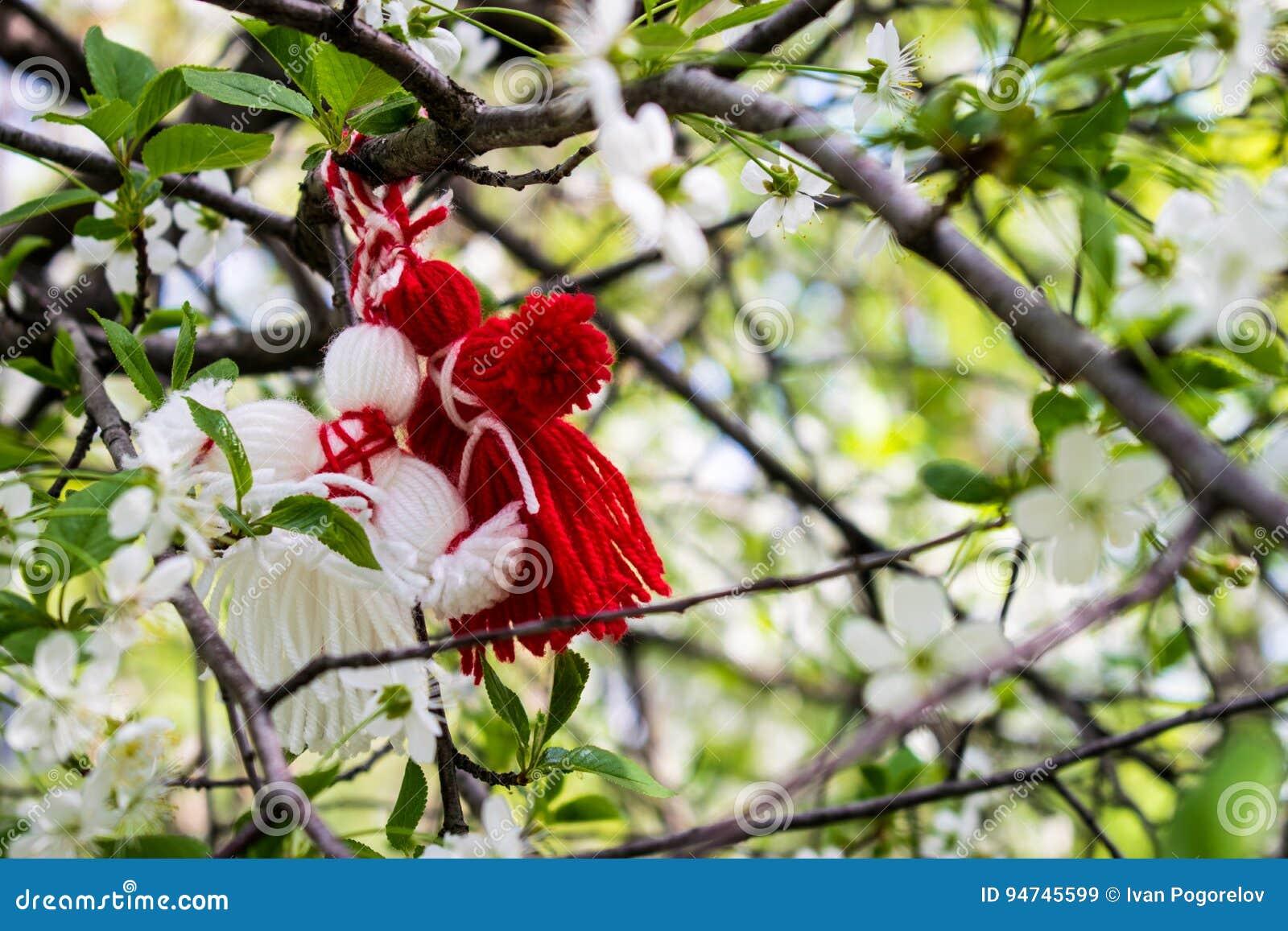 Två trasdockor av röd och vit färg som hänger bland de vita blommorna, är körsbär med gröna sidor
