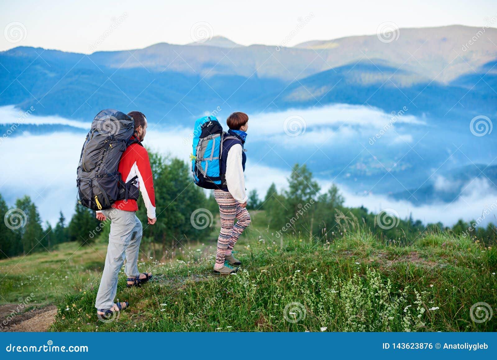 Två turister med ryggsäckar i vandring på berg av Carpathians