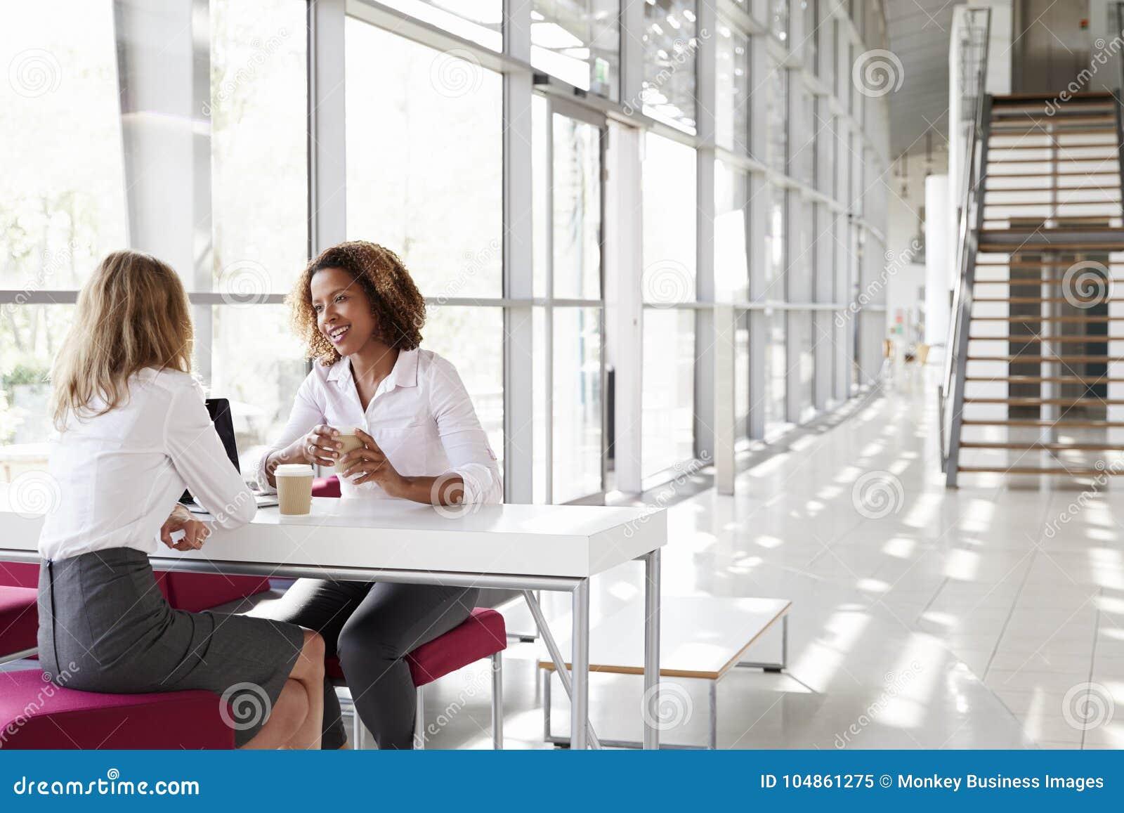 Två unga affärskvinnor på ett möte som talar