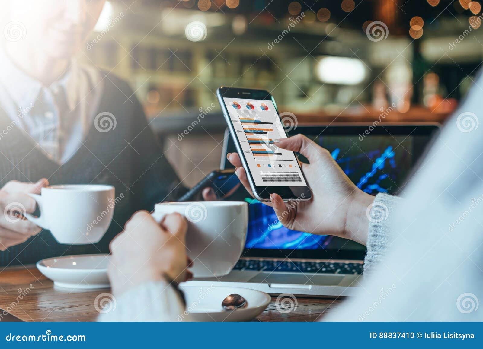 Två unga affärskvinnor som sitter på tabellen, dricker kaffe och analyserar data På tabellbärbara datorn Studenter som direktansl