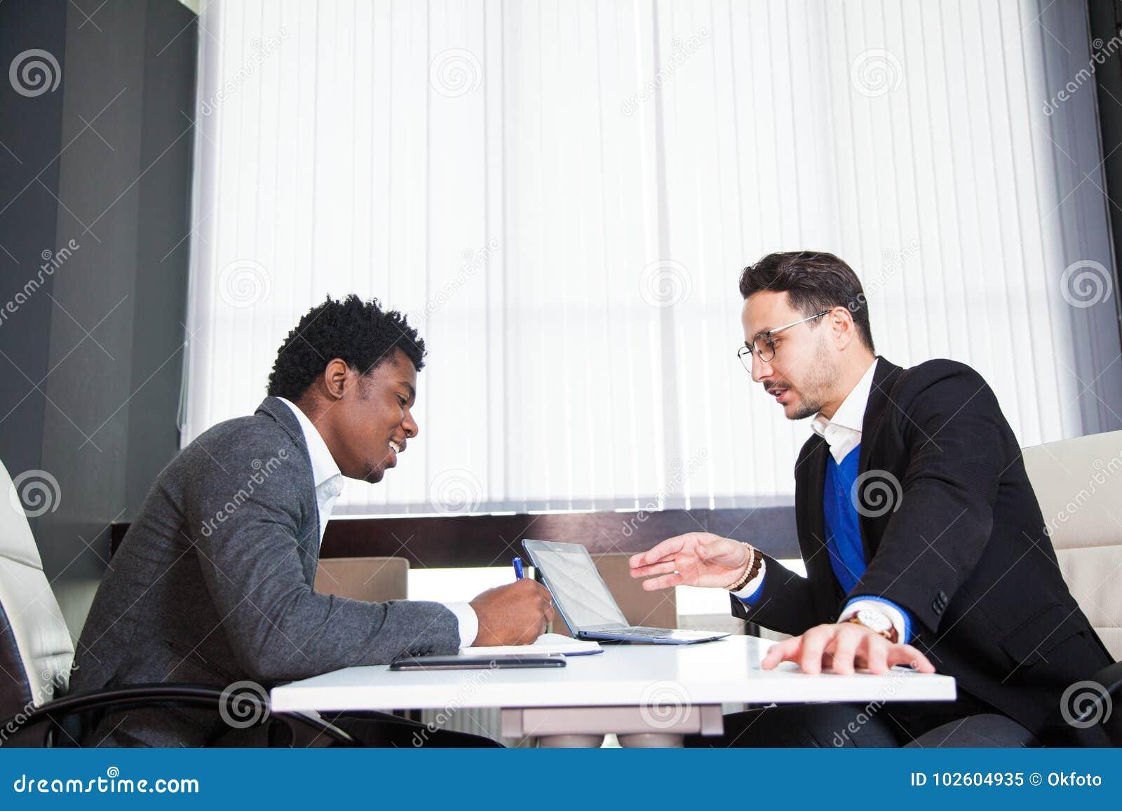 Två unga affärsmän, vitt skrivbord, jobbintervju, teamwork