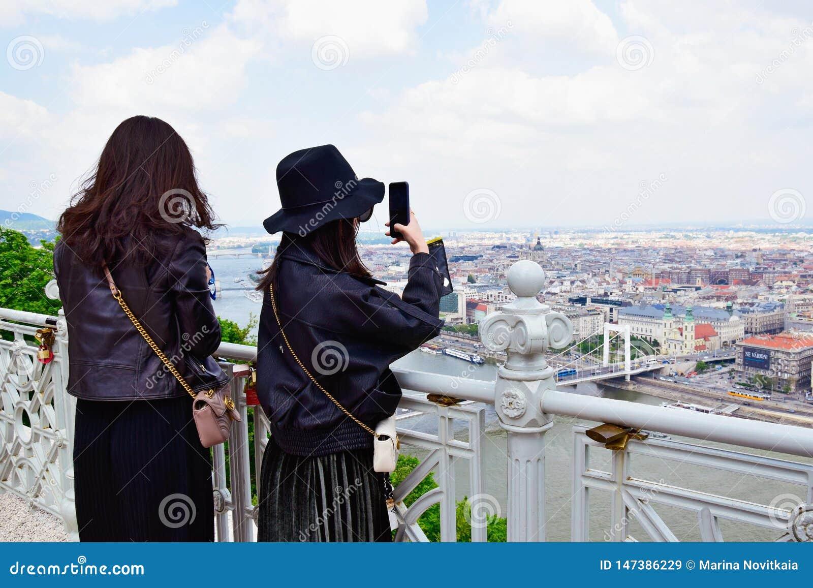 Två unga asiatiska kvinnor som tar bilder av de sceniska sikterna av Budapest
