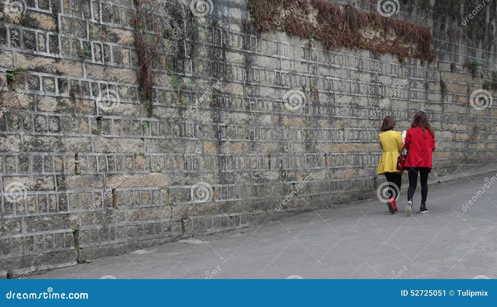 Två unga damer som går på den Gulangyu ön i Kina