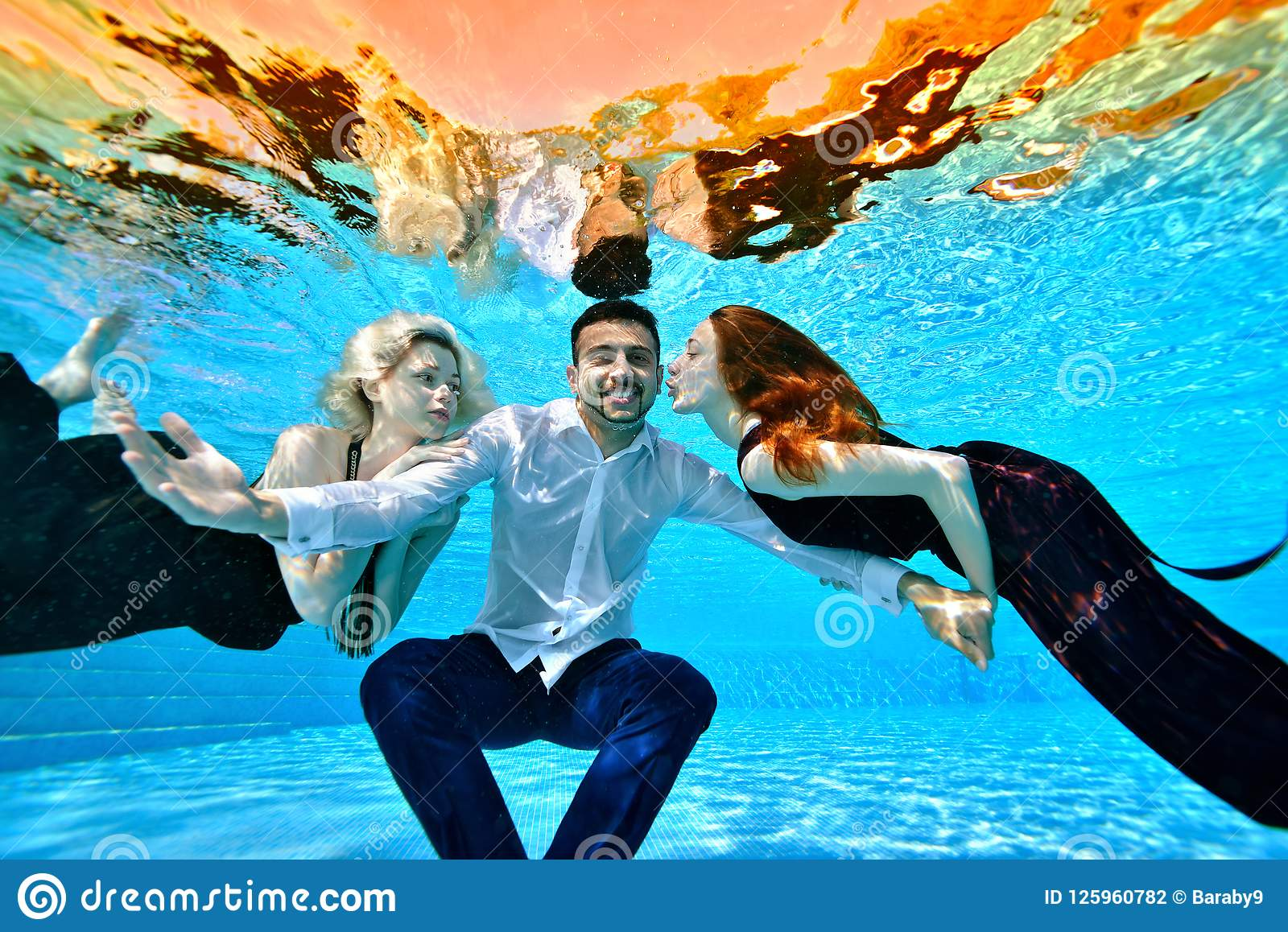 Två unga flickor som är förälskade, en blondin och en brunett, bad i klänningar och lek med en grabb i en vit skjorta under vatte