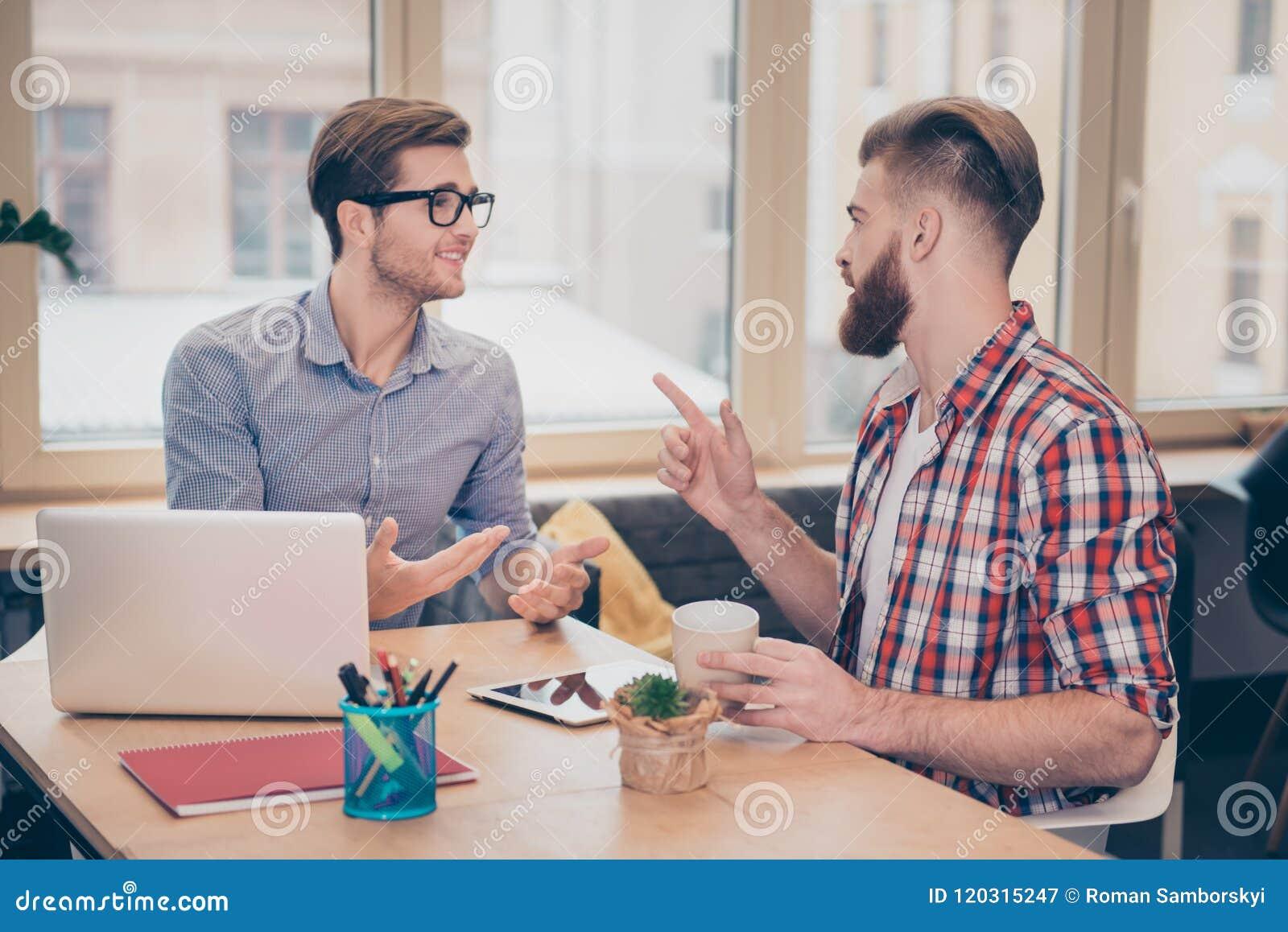 Två unga freelancers som direktanslutet arbetar på projekt, planerar bästa vän som talar ha konversation i kafét som ser de gestu