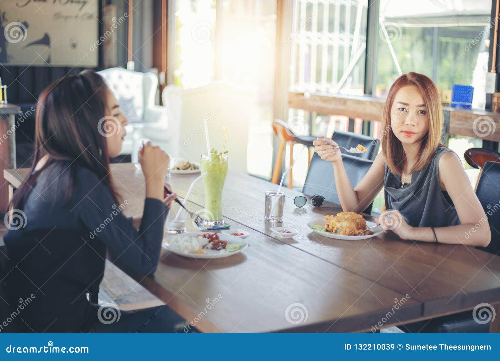 Två unga kvinnliga vänner skrattar och ha lunch tillsammans på Rest