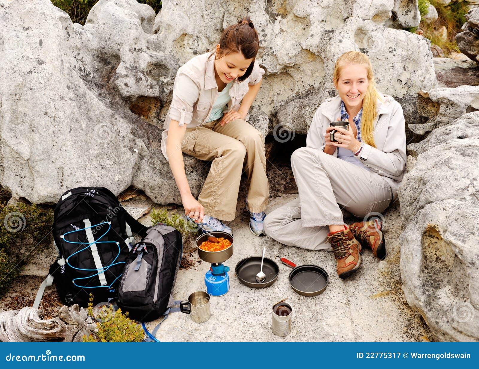 Två unga kvinnor förbereder något att äta