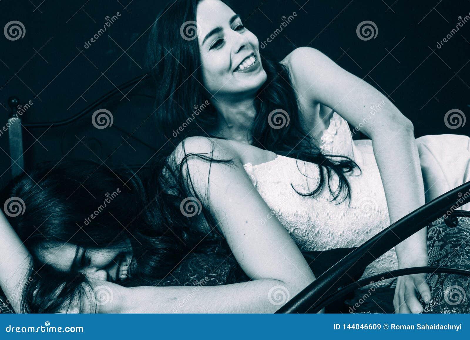 Två unga kvinnor i tappningdamunderkläder på den spridda sängen mot den svarta väggen, förälskelselekar, smekning, kysser Tillfog