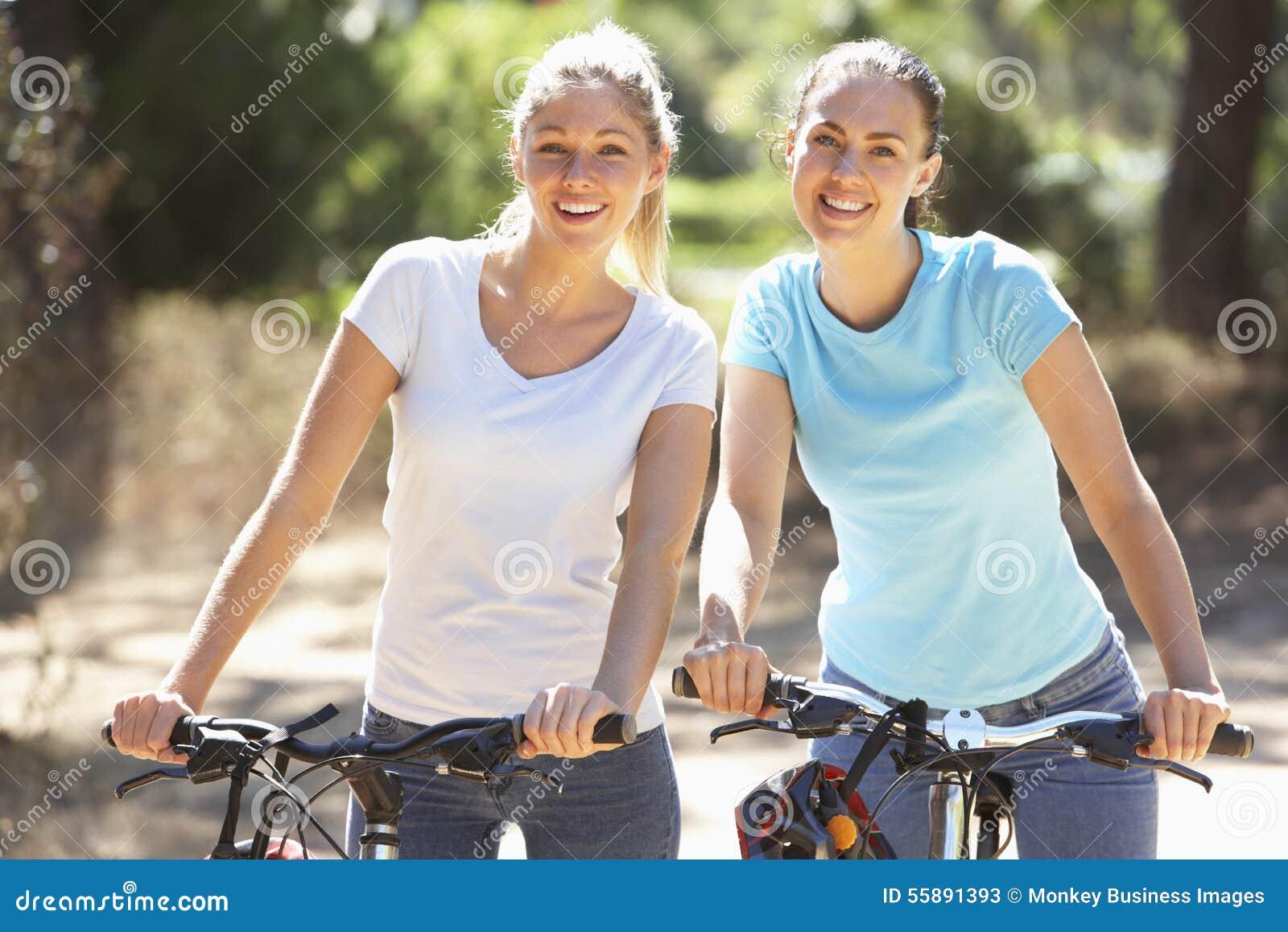Två unga kvinnor på cirkulering rider tillsammans