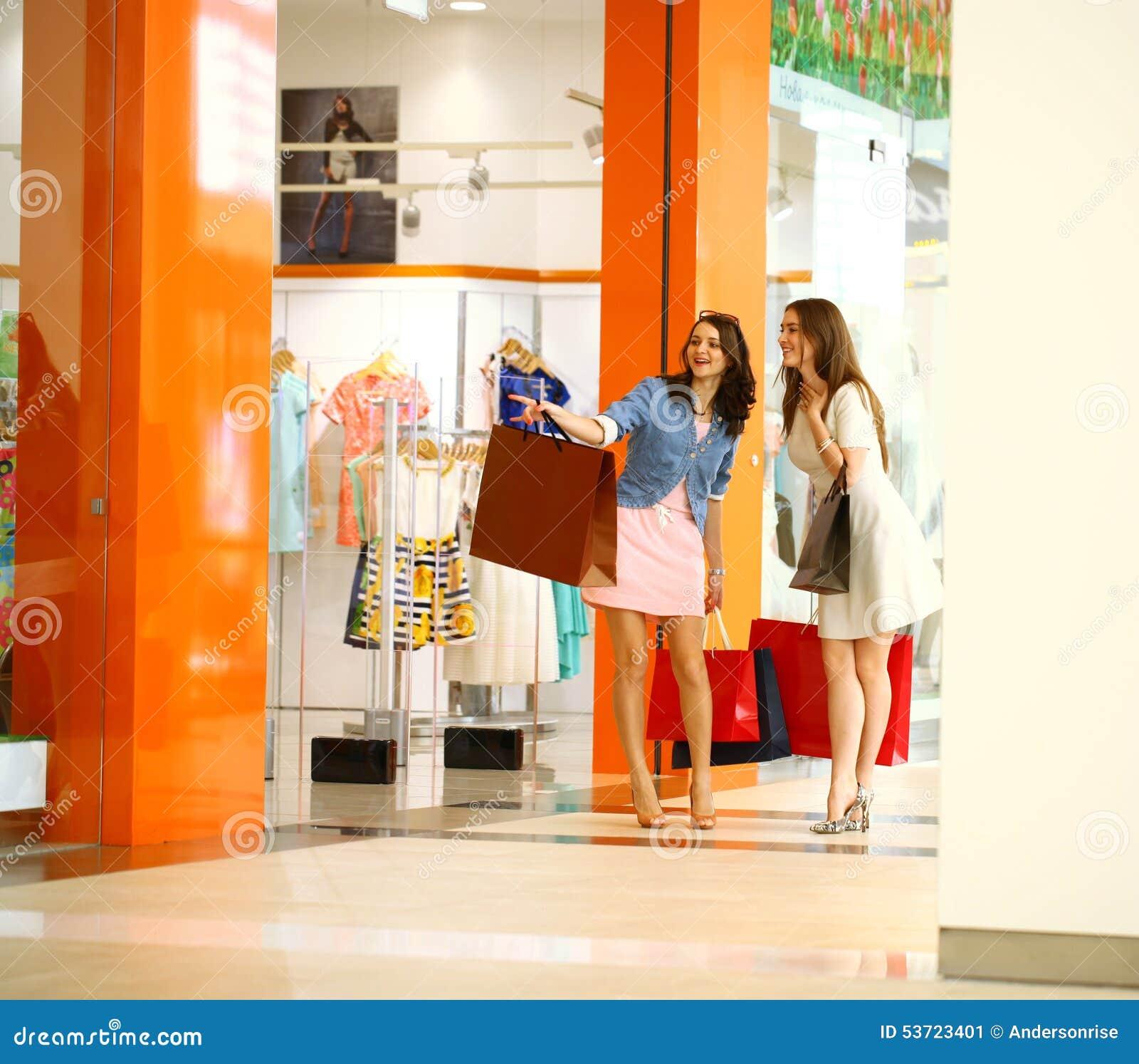 Två unga kvinnor som går med shopping på lagret