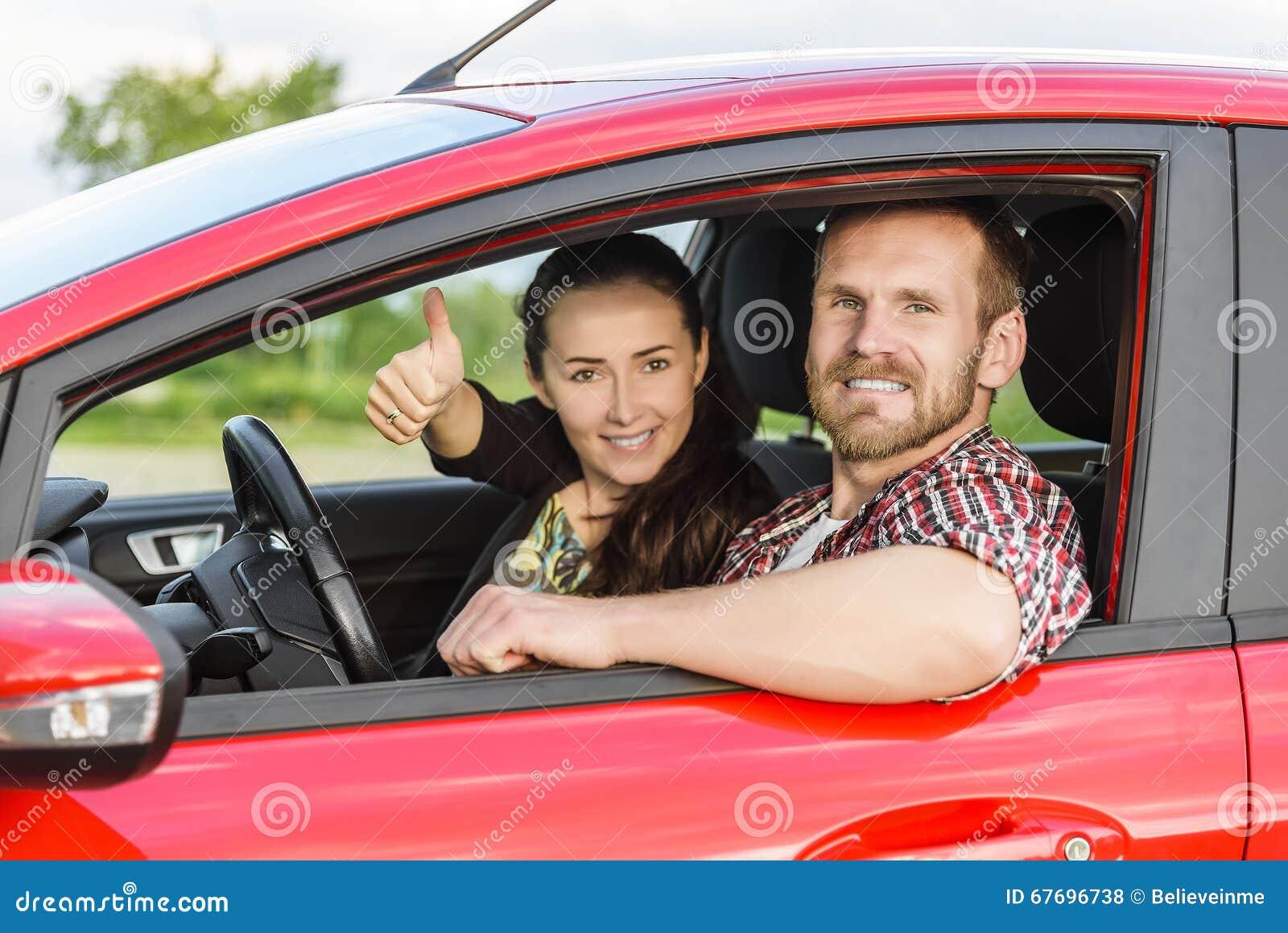 Två unga le personer i en röd bil