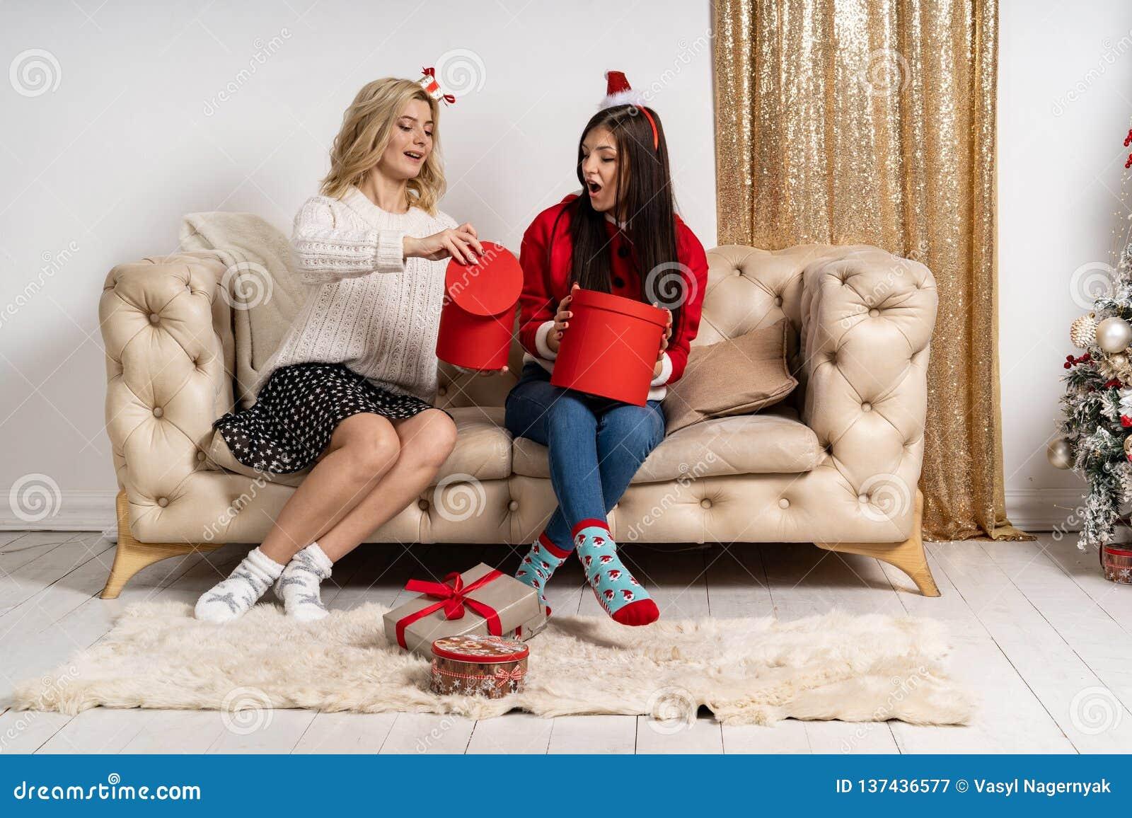 Två unga lyckliga flickor i stilfulla tröjor och santa hattar