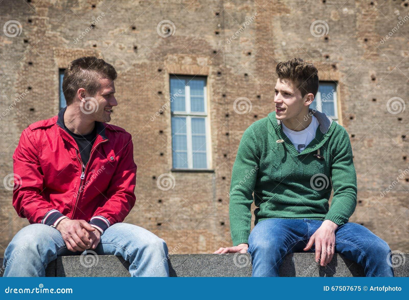 Två unga män som talar, medan sitta på trottoarkant