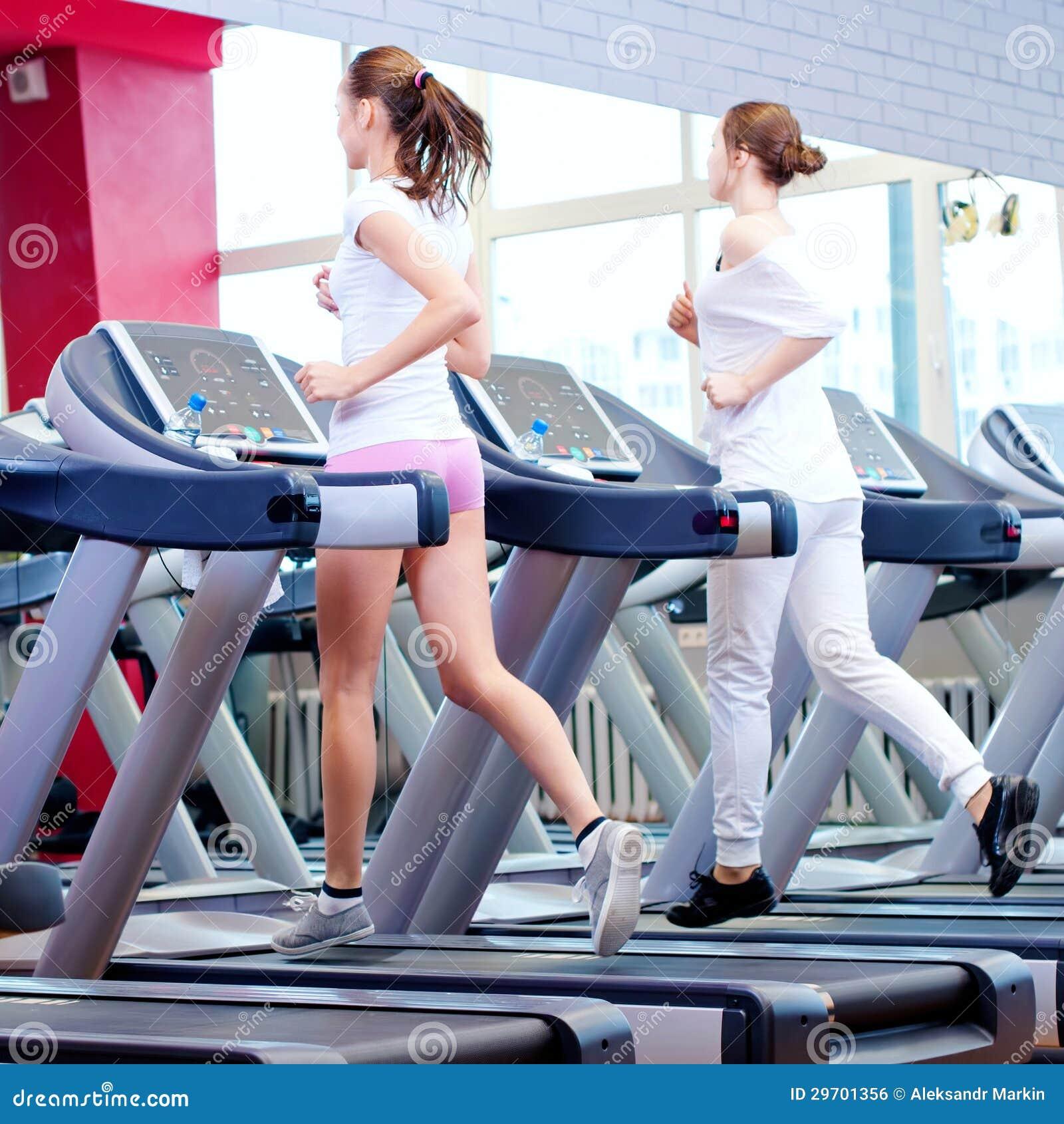 Två unga sportiga kvinnor som körs på maskinen