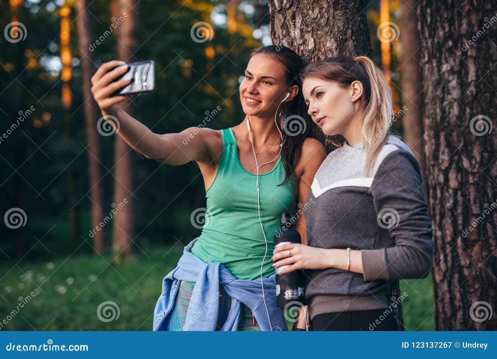 Två unga sportive flickvänner som bär sportswearbenägenhet mot trädet som tar selfie med smartphonen i skog