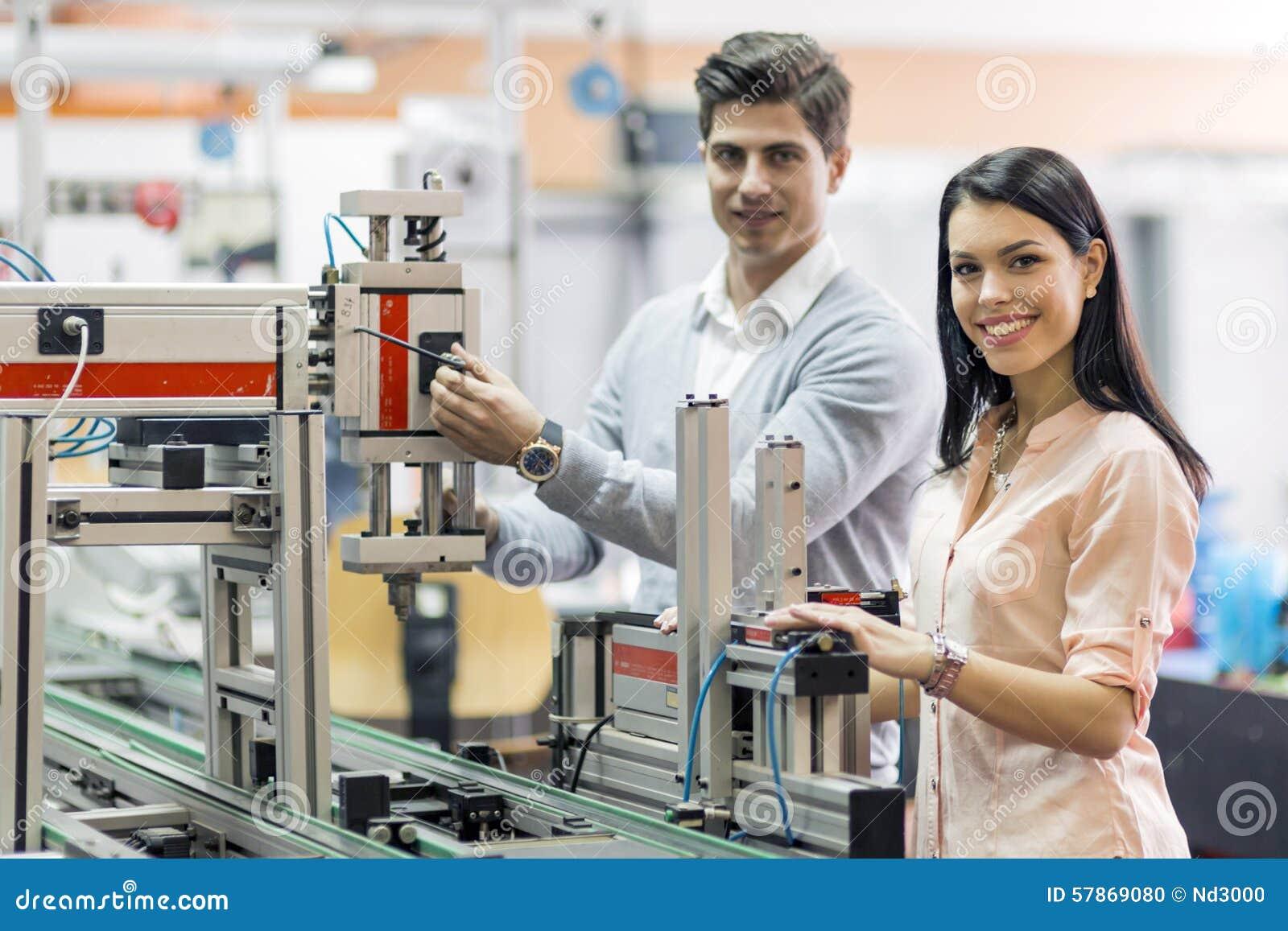 Två unga studenter som tillsammans arbetar på ett projekt i labb