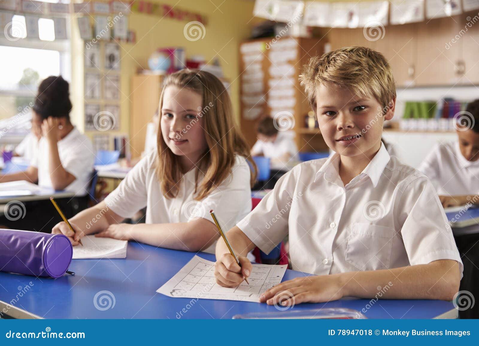 Två ungar i en kurs på en grundskola för barn mellan 5 och 11 år ser till kameran