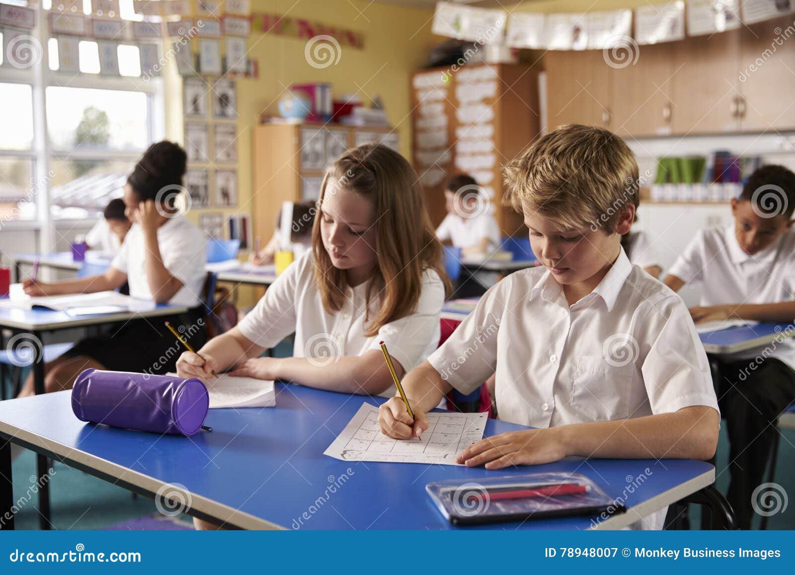 Två ungar som arbetar på skrivbord i ett grundskola för barn mellan 5 och 11 årklassrum