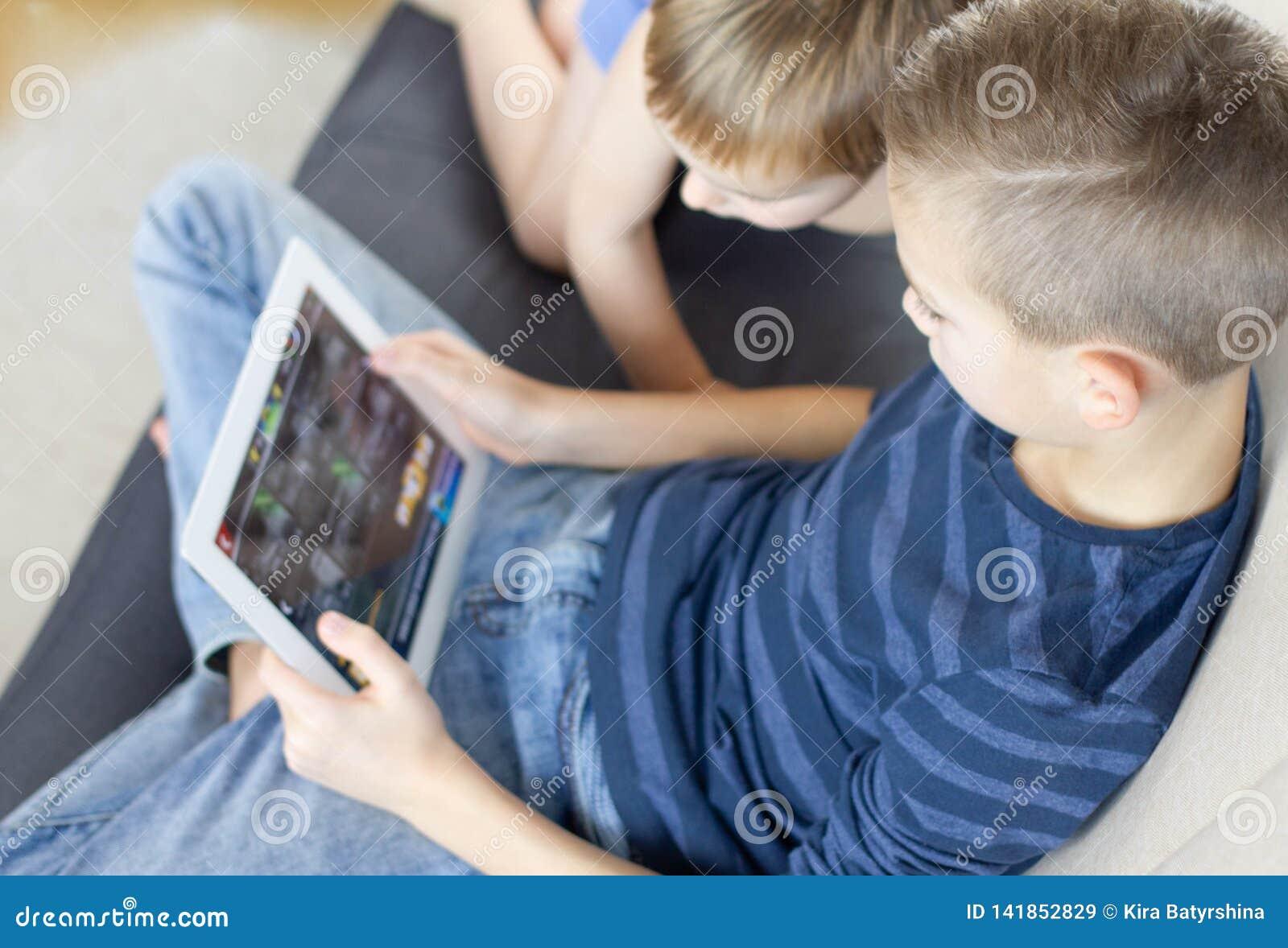 Två ungar som hemma använder minnestavlan Bröder med minnestavladatoren i ljust rum Pojkar som spelar lekar på minnestavlaPC, sin
