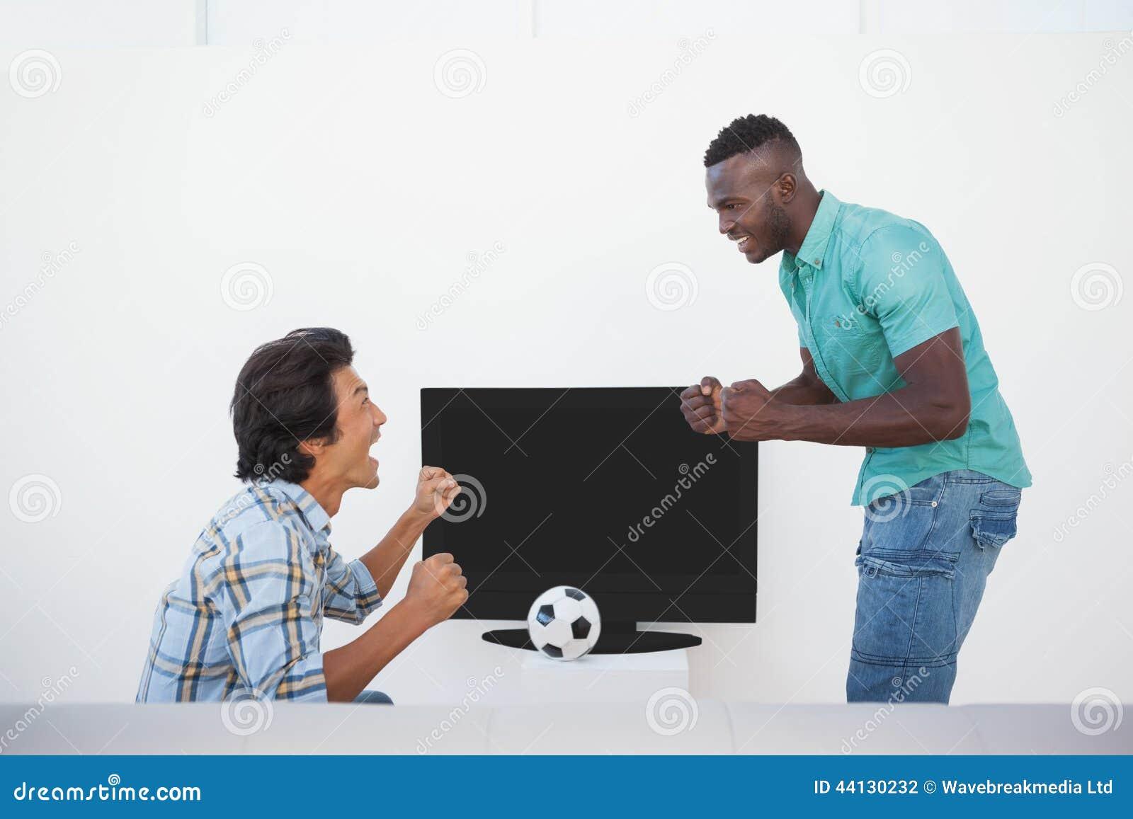 Två upphetsade fotbollfans som håller ögonen på tv