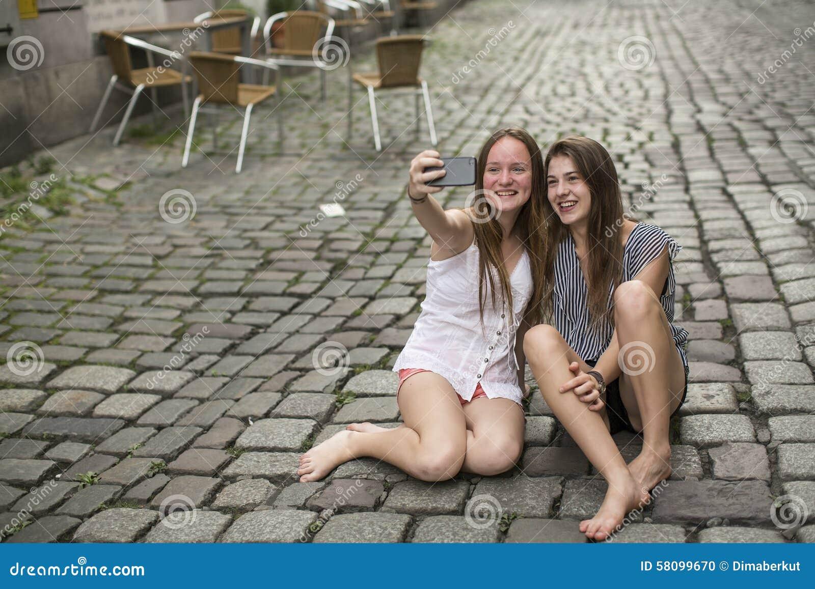 Två uppsluppna tonårs- flickor gör selfie på telefonsammanträdet på trottoaren