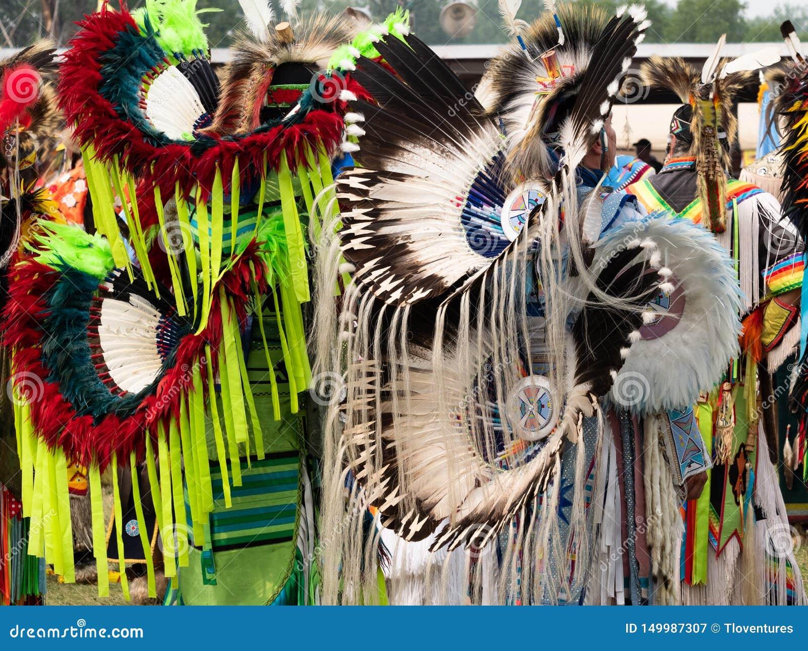 Två utsmyckade dansare för indian som väntar för att dansa på en Pow, överraskar
