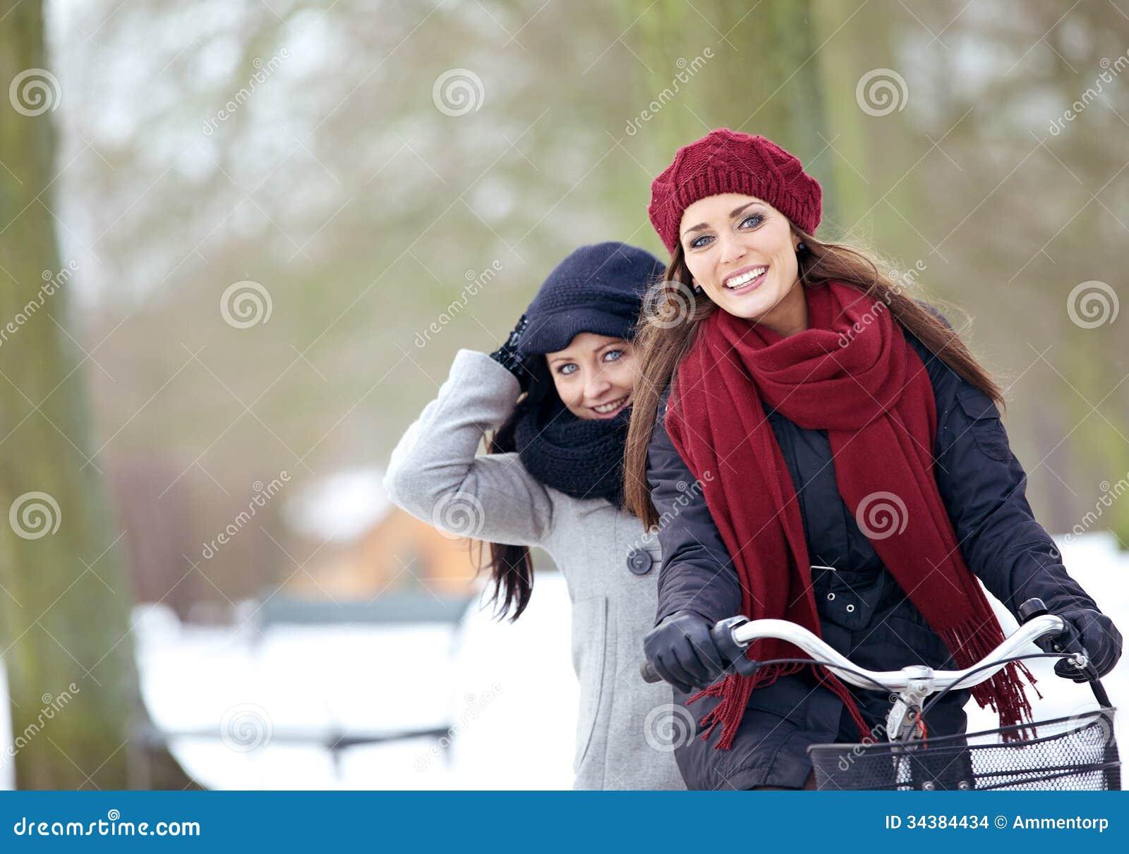 Två vänner som utomhus tycker om vintersemestern