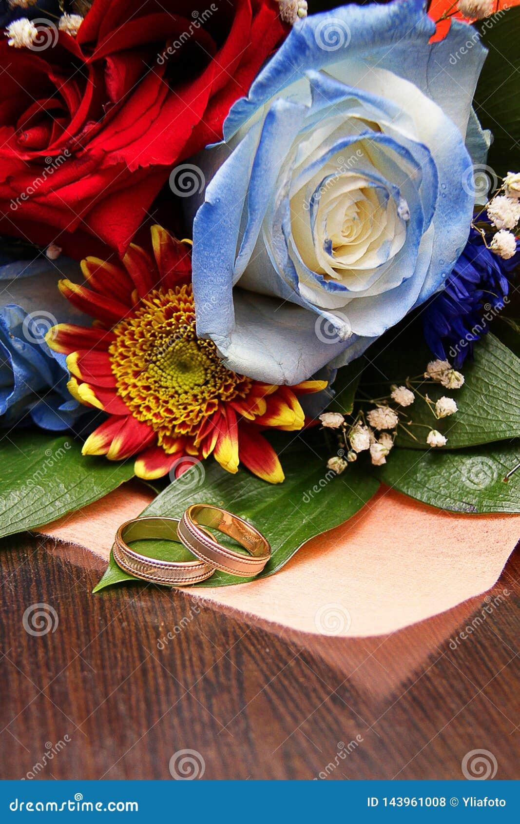 Två vigselringar mot bakgrunden av en brud- bukett från en blå ros och röda färger