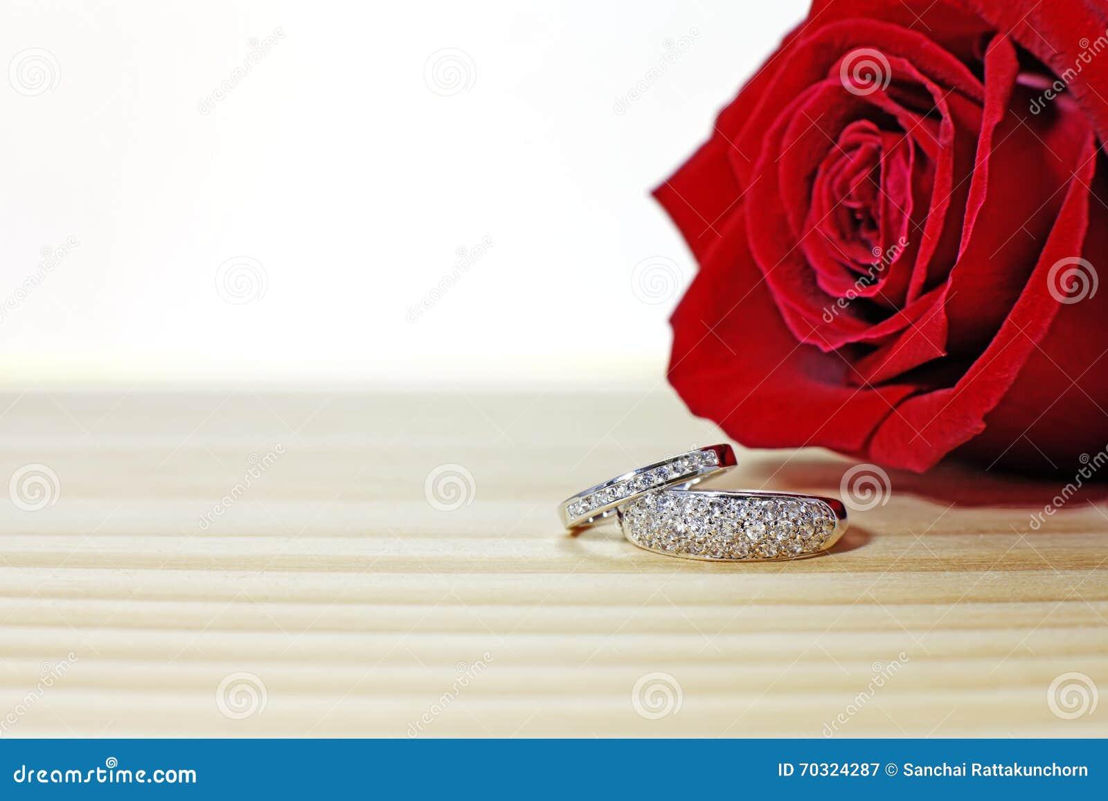 Två vigselringar på trätabellen med mörker - röd ros
