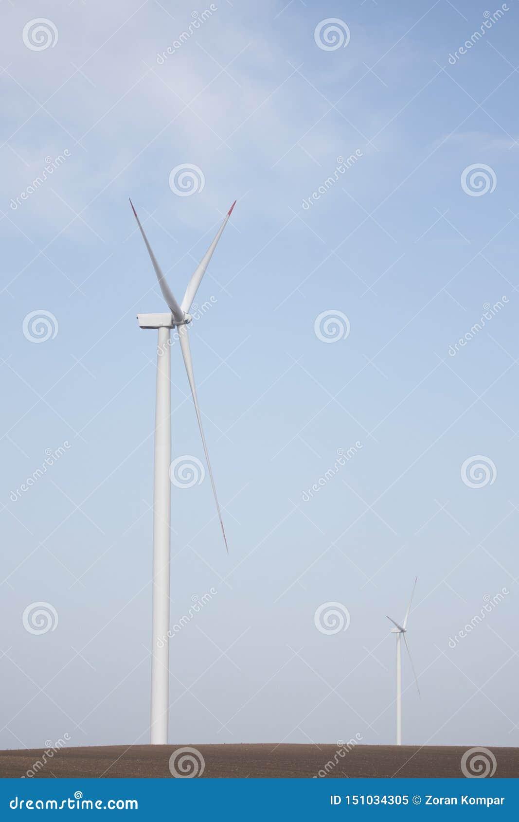 Två vindturbiner på jordbruks- jordning med klar himmel i bakgrund