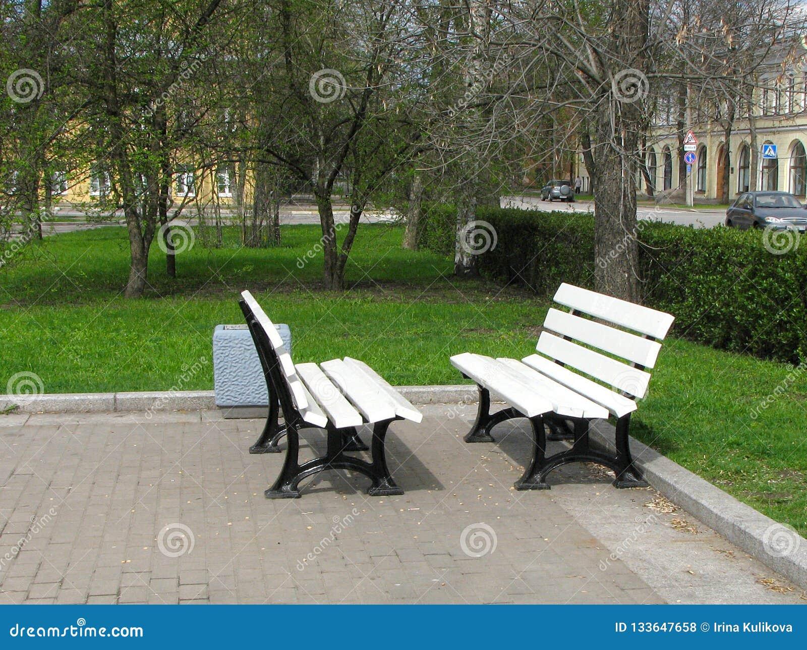 Två vita bänkar står mitt emot de i parkerar Tar av planet