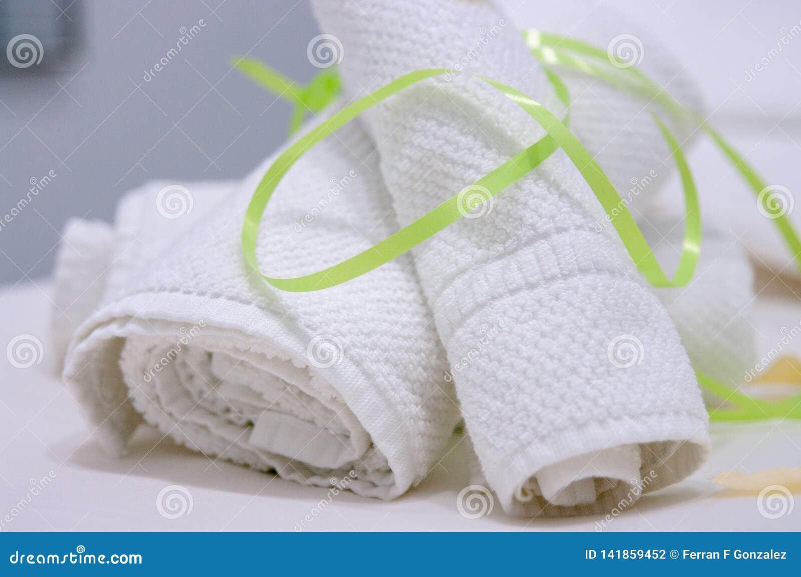 Två vita handdukar rullande och som fästs med det gröna bandet på massagetabellen