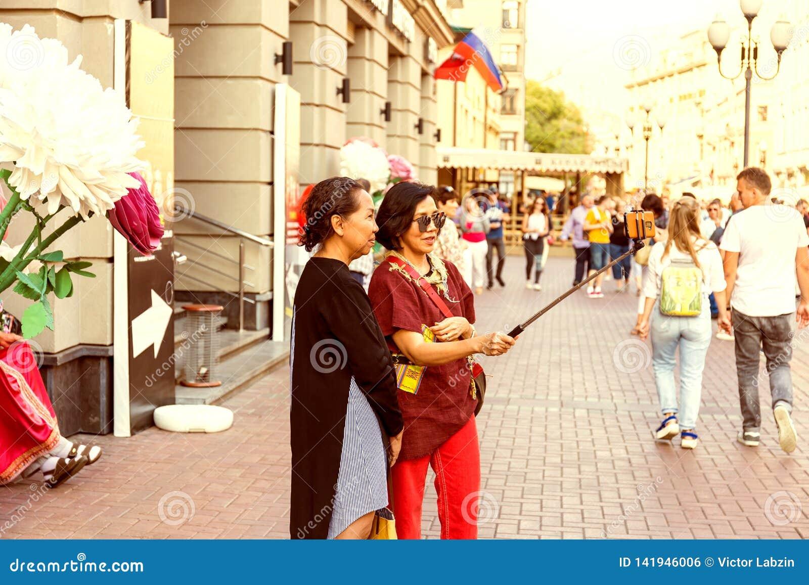 Två vuxna asiatiska kvinnor som tar en selfie genom att använda smartphonen