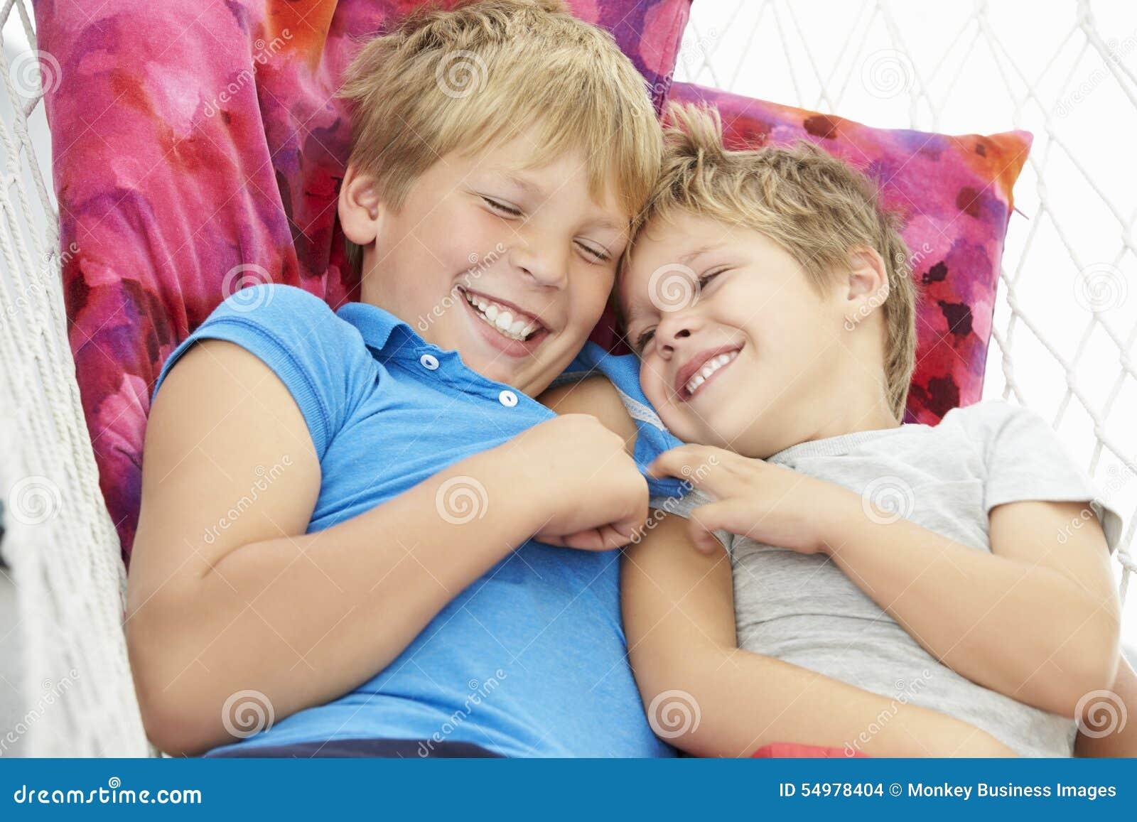 Två Young Boys som tillsammans kopplar av i trädgårds- hängmatta